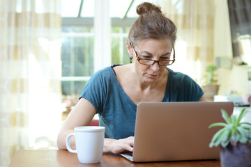 Elderly woman with glasses works in laptop at home office