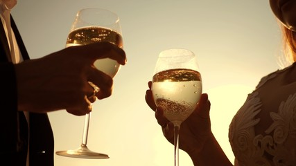 couple in love holding wine glasses with sparkling wine on background of sunset. close-up. teamwork of loving couple. celebrating success and victory. champagne sparkles and foams in sun. Slow motion