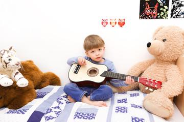 Ein kleiner Junge spielt auf einer Gitarre