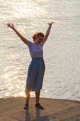 Fröhliche Jugendliche am Fluss am Abend hält Hände hoch