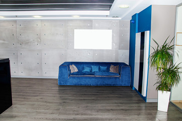 Trendy gray interior with blue sofa with blue and gray pillows in the reception office