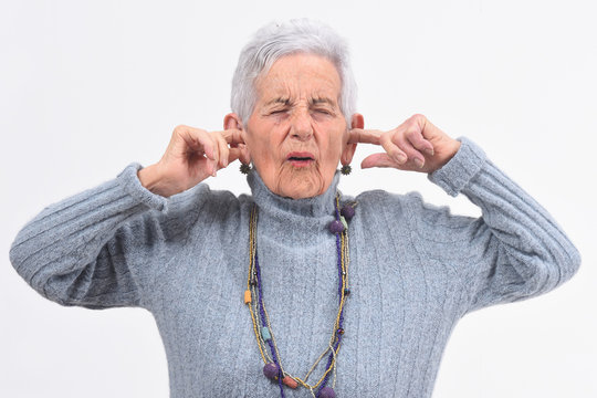 senior woman making noise hurting her ears on white background