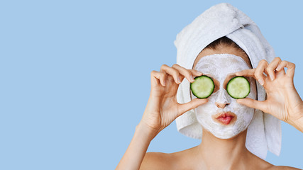 Beautiful young woman with facial mask on her face holding slices of cucumber. Skin care and treatment, spa, natural beauty and cosmetology concept. Wall mural