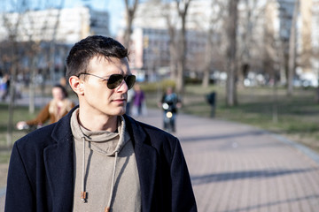 Portrait of young man with sunglasses and black coat outdoor in the park