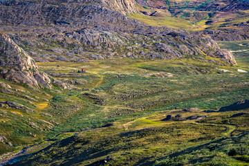 Hiking in the arctic - the Arctic Circle Trail (ACT) during summer in Greenland - small red hut in distance with beautiful landscape views, grass, mountains, sky