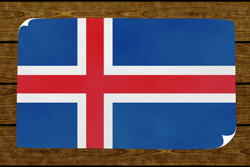 Graphic illustration of an Icelandic flag painted on the paper pasted on the woody wall
