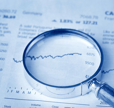 magnifying glass on financial newspaper