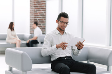 modern man uses a digital tablet sitting in the office lobby.