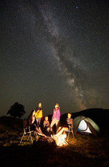 Group of friends hikers having a rest together in summer camping, beside bonfire and illuminated tourist tent at night. Guys enjoying night starry sky full of stars and Milky way in the mountains