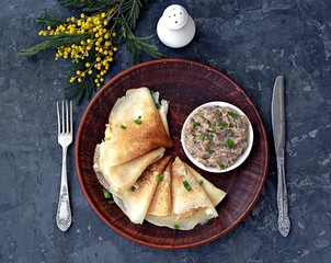 Thin pancakes on a clay brown plate. Served with forshmak, a snack made from chopped salted herring, eggs and onions. Top view.