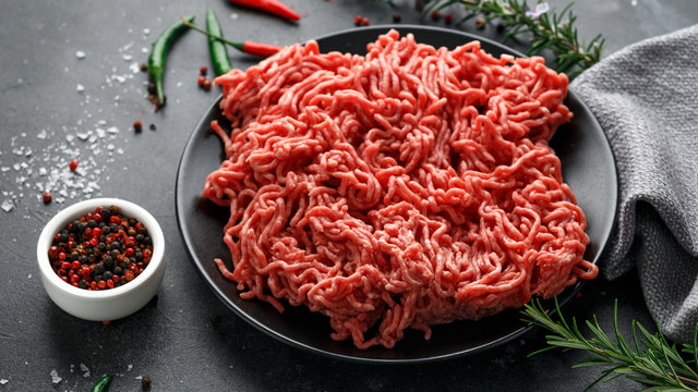 Fresh Raw mince, Minced beef, ground meat with herbs and spices on black plate