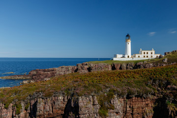 Rua Reidh lighthouse with keepers house on a rocky, grassy coastline with blue sky.