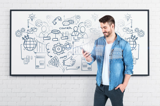 Man looking at smartphone business plan whiteboard