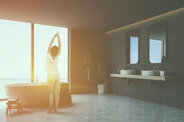 Woman in gray tile bathroom corner, tub and sinks