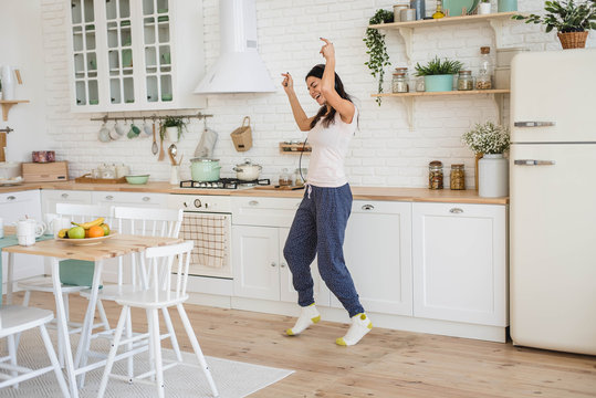 Young happy beautiful woman dancing in kitchen in pajamas and headphones, listening to music