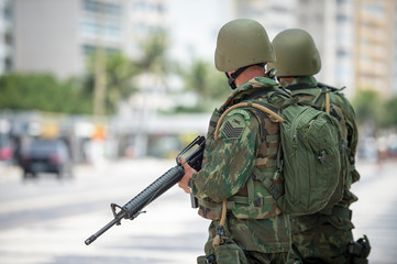 Two Brazilian Army soldiers standing in full camouflage uniform on the boardwalk at Copacabana Beach in Rio de Janeiro, where crime is a persistent problem
