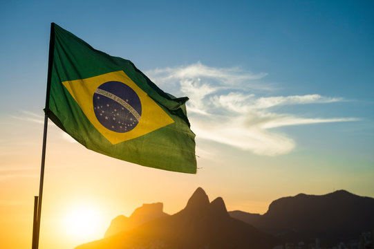 Brazilian flag waving backlit in front of the golden sunset mountain skyline at Ipanema Beach in Rio de Janeiro, Brazil