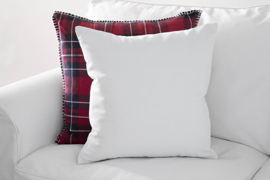 Mockup of white square cushion with red plaid square cushion on a white sofa.