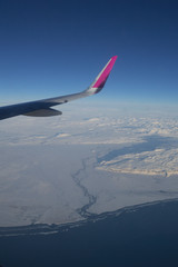 Aerial View of Iceland Coastline with Wing of Plane in Flight