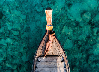 Aerial drone shot of a young brunette woman without bra in the front of a wooden boat. Crystal clear water and corals at a tropical island and amazing beach.