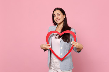 Portrait of smiling pretty young woman in striped jacket holding big red wooden heart isolated on pink pastel wall background in studio. People sincere emotions, lifestyle concept. Mock up copy space.