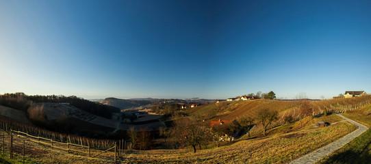 Hügellandschaft panorama im Herbst oder Frühling mit blauem Himmel. Hilly landscape in spring or fall with blue sky.