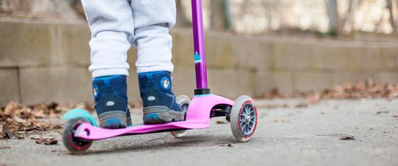 Kid on little pink scooter. Kind auf pinkem Roller.