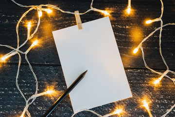 notepad and pencil on wooden desk with copyspace to add you text surrounded by fairy lights