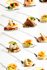 Background of mixed canapes on metal spoons. White background.