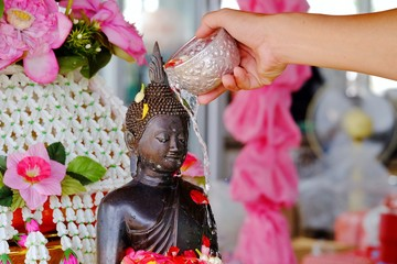 A male hand pouring flower water on a monk statue at the Buddha temple for Songkran festival in Thailand