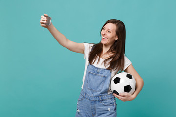 Smiling young woman football fan with soccer ball doing selfie shot on mobile phone isolated on blue turquoise background. People emotions, sport family leisure lifestyle concept. Mock up copy space.