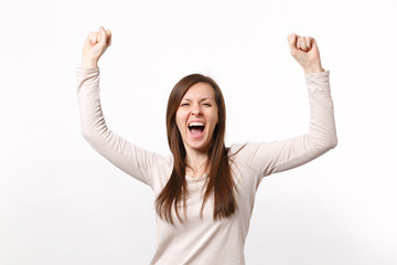 Portrait of happy screaming young woman in light clothes rising hands, doing winner gesture isolated on white wall background in studio. People sincere emotions, lifestyle concept. Mock up copy space.