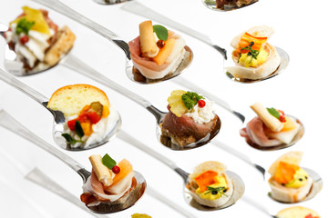 Closeup of mixed canapes on metal spoons. White background.