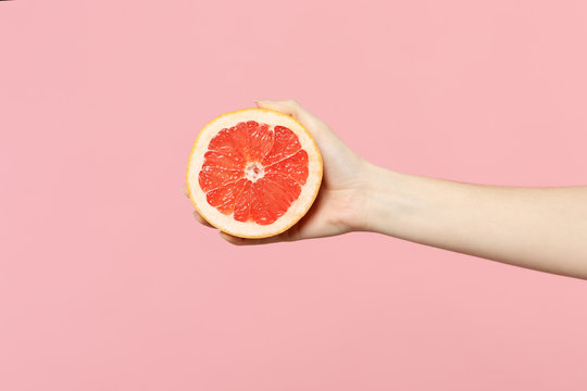 Close up cropped photo of female hold in hand fresh ripe half grapefruit fruit isolated on pink pastel wall background. Copy space advertising mock up. People vivid lifestyle, relax vacation concept.