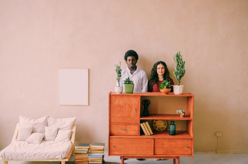 Indoor lifestyle portrait of odd happy interracial loving couple standing together beyond wall behind bureau. Strange loving family at home. Dark skinned man in love with white woman. Room interior.