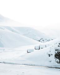 Houses next to snowy mountains