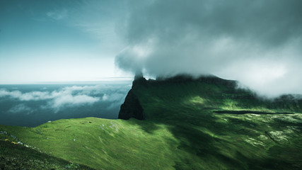 Low cloud rolls over green cliffs, Iceland