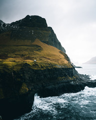Tiny building on cliff overlooking water