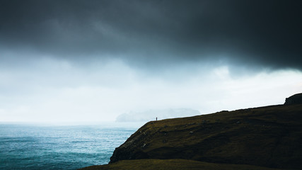 Person stands on a cliff under storm clouds