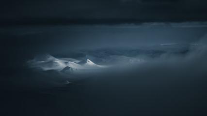 Snowy mountain peaks illuminated in a dark landscape