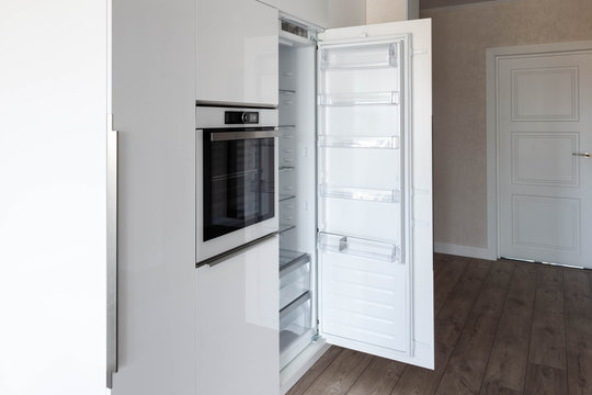 Opened integrated build-in refrigerator in a white glossy kitchen. Perfect way to hide kitchen appliances.