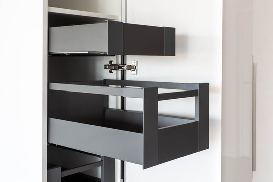 Opened kitchen cabinet with inner drawers inside in white and grey colors