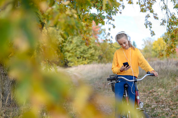 Smiling girl with headphones sitting on bicycle looking at smartphone