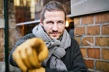 Portrait of bearded young man wearing scarf and gloves pointing on viewer