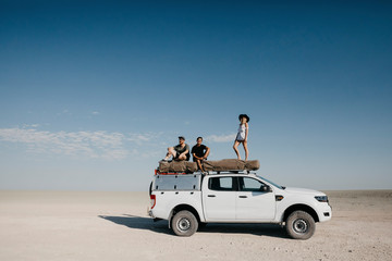 Friends on a safari, standing on their off-road vehicle
