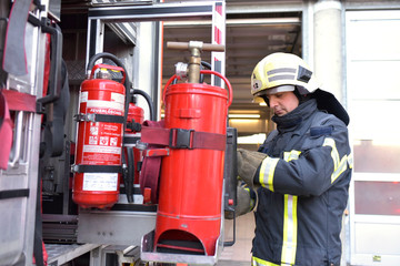 Firefighter standing at fire engine with fire extinguisher