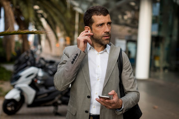 Businessman with cell phone in the city applying earbuds