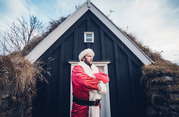 Iceland, Santa Claus standing in front of cabin looking at distance
