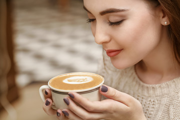 Loving the smell. Closeup shot of a gorgeous young woman smelling her coffee smiling cheerfully