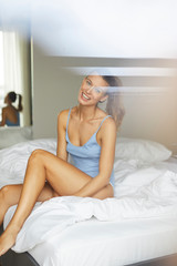 Portrait of happy young woman sitting on bed